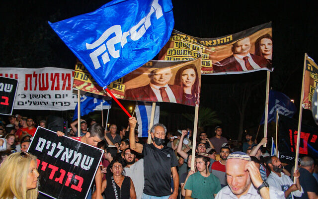 """Demonstrators outside the home of Yamina's Ayelet Shaked hold placards denouncing Yamna's planned coalition with the centrist Yesh Atid and other parties that would end Benjamin Netanyahu's 12-year prime ministership. The sign at bottom left reads: """"Leftists. Traitors."""" (Flash 90)"""