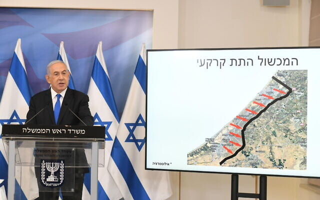Prime Minister Benjamin Netanyahu gives a statement at a press conference after the Gaza ceasefire, Tel Aviv, May 21, 2021. At his side is a screen showing Israel's subterranean barrier surrounding the Gaza Strip (Amos Ben Gershom/GPO)