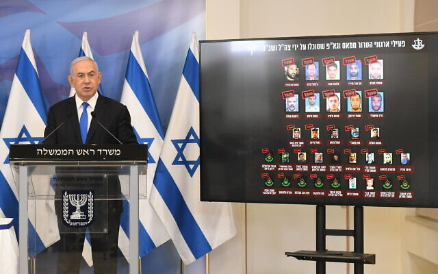 Prime Minister Benjamin Netanyahu gives a statement at a press conference after the Gaza ceasefire, Tel Aviv, May 21, 2021. At his side is a screen showing Gaza terror commanders killed in Operation Guardian of the Walls (Amos Ben Gershom/GPO)