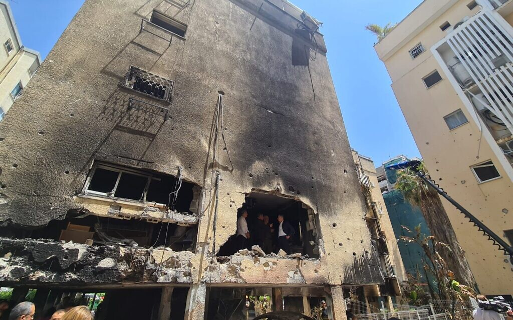 German Foreign Minister Heiko Maas tours a Petah Tikva building hit by Hamas rocket fire, along with Foreign Minister Gabi Ashkenazi and head of the IDF Home Front Command, Ori Gordin, May 20, 2021 (Foreign Ministry)