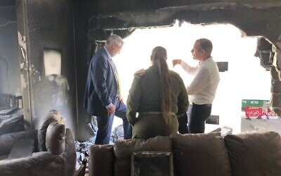 Indiana Gov. Eric Holcomb (left) surveys the wreckage of a Petah Tikva apartment hit by Hamas rocket fire, May 21, 2021. (Lazar Berman/Times of Israel)