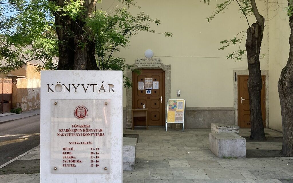 Exterior of the Baroque style synagogue of Nagyteteny, which now serves as a public library. An inscription in Hebrew and Hungarian remains preserved above the doorway, May 11, 2021. (Yaakov Schwartz/ Times of Israel)