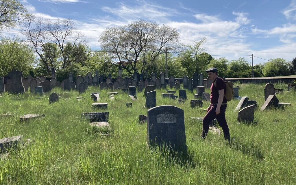 Matyas Kiraly walks among toppled and vandalized gravestones in the ancient Jewish cemetery in Nagyteteny, May 11, 2021. (Yaakov Schwartz/ Times of Israel)