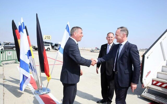 Foreign Minister Gabi Ashkenazi (L) greets German Foreign Minister Heiko Maas (R) at Ben Gurion Airport, May 20, 2021 (Miri Shimonovitch)