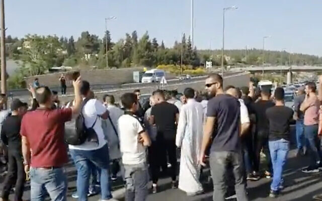 Arab Israelis block traffic on Route 1 after the buses they were traveling on were stopped en route to Jerusalem, amid rising violence in the city, on May 8, 2021. (Screen capture: Twitter)