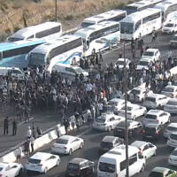 Arab Israelis block traffic on Route 1 after the buses they were traveling on were stopped en route to Jerusalem, amid rising violence in the city, on May 8, 2021. (Screen capture)