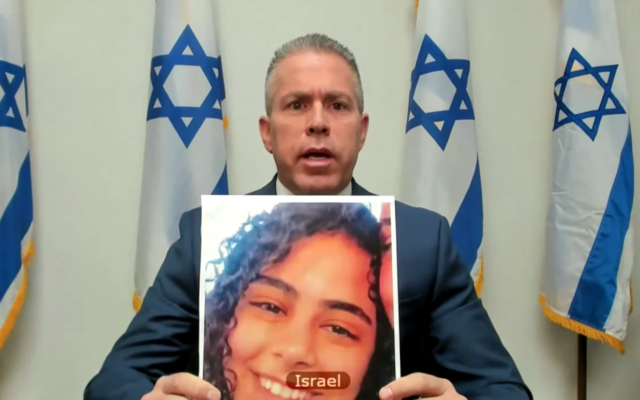 Israeli UN envoy Gilad Erdan holding up a picture of Nadin Awad, who was killed by a Hamas rocket, at a UN Security Council virtual meeting on May 16, 2021. (screen capture: UN TV)