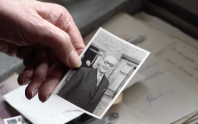 Dr. Robert G. W. Anderson's hand showing a photo of his grandfather, who fled Austria in the Holocaust, in a video produced by AFP on March 19 2021. (Screen capture: AFP)