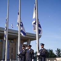 The Knesset Guard lowers Israeli flags to half-staff outside the Knesset in Jerusalem as a national day of mourning begins for victims of the Meron disaster, May 2, 2021. (Noam Moskowitz/Knesset)