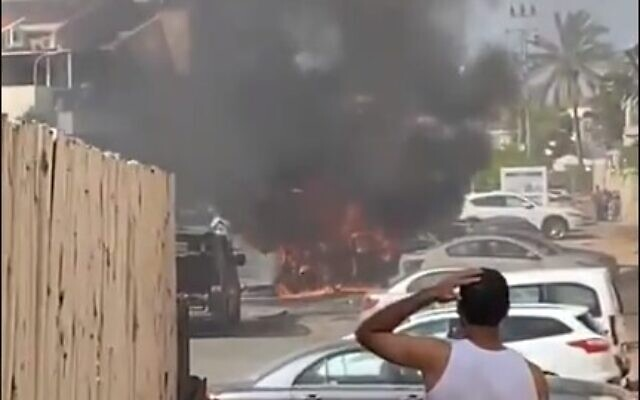 A vehicle on fire after being struck by a rocket in Ashkelon on May 16, 2021. (screen capture: Twitter)
