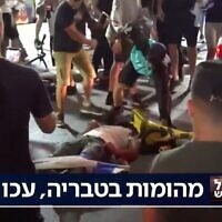 A man beats a man lying prone on the ground in Bat Yam, amid interethnic violence across Israel, May 12, 2021. (Kan TV Screenshot)