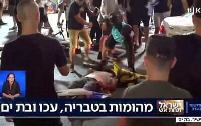 A man beats a man lying prone on the ground in Bat Yam, amid interethnic violence across Israel, May 12, 2021. (Kan TV Screenshot)
