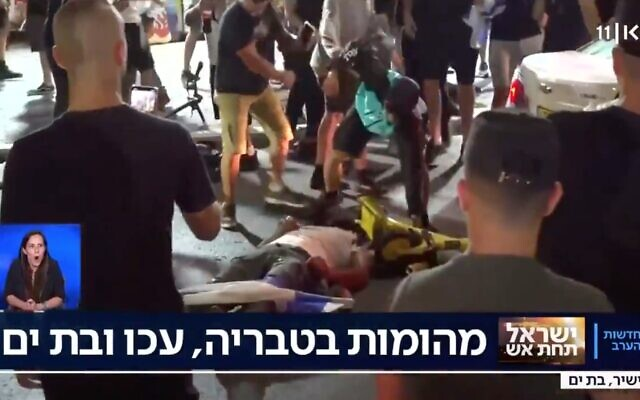 A man beats someone lying prone on the ground in the Israeli city of Bat Yam amid interethnic violence across Israel, May 12, 2021. (Screenshot)