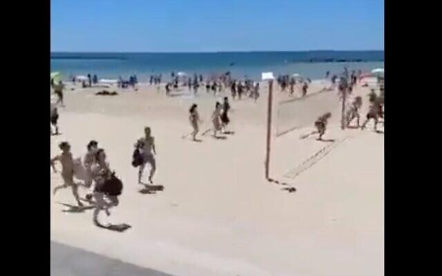 Israeli on Tel Aviv beach run for shelter as sirens signal incoming rockets from Gaza on May 15, 2021 (Twitter screenshot)
