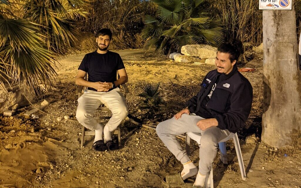 Hilal (right) and Khalil Habashi sit guard outside their Ajami home, May 19, 2021. (Elie Bleier)