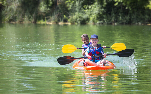 Illustrative: Two boys kayaking down a river at summer camp (Yobro10; iStock by Getty Images)