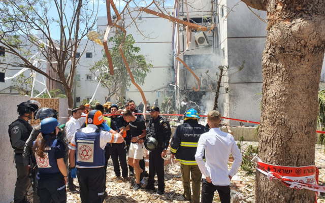 Rescue services are seen at a building in the southern port city of Ashdod that was hit by a rocket fired by Palestinian terrorists in the Gaza Strip, May 17, 2021. (Magen David Adom of Ashdod)