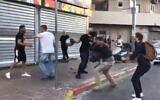 Reporters for the Kan public broadcaster are beaten in the Tikva neighborhood of Tel Aviv, May 13 , 2021 (Screen grab/Twitter)