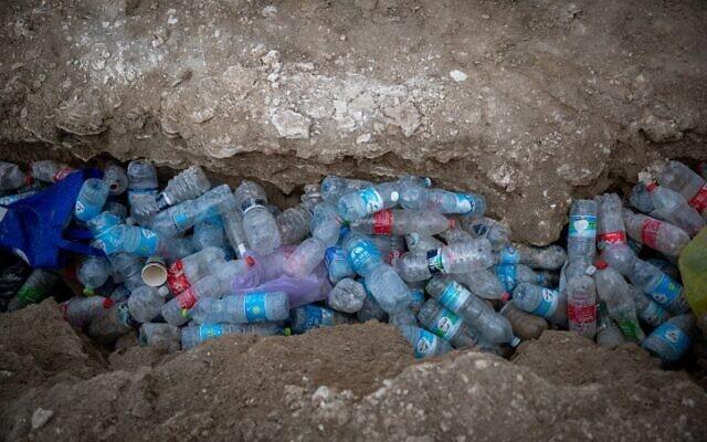 Empty plastic bottles lie strewn on a Dead Sea beach, November 5, 2020. (Yonatan Sindel/Flash90)
