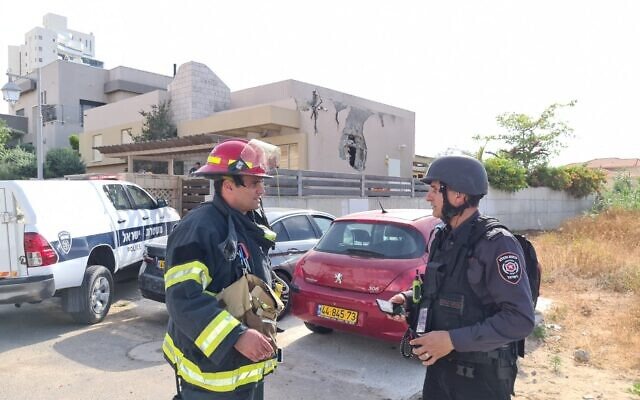 Fire service officials outside an Ashkelon synagogue hit by a rocket, May 16, 2021 (National Fire and Rescue Authority)