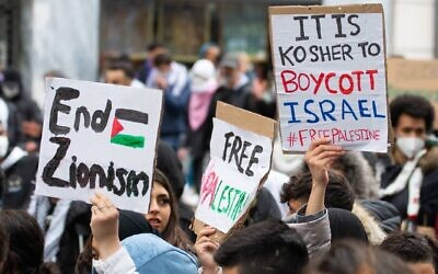 Illustrative: Demonstrators against Israel hold signs at a rally in Vienna, Austria, where protesters chanted in Arabic about a massacre of Jews, May 13, 2021. (Courtesy of Austrian Union of Jewish Students via JTA)