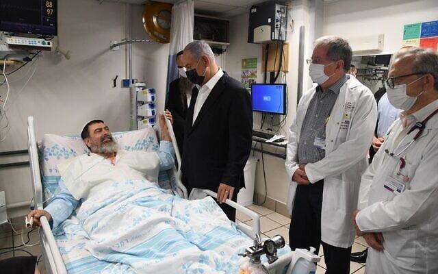 Prime Minister Benjamin Netanyahu visits a man injured in the Mount Meron disaster, at Haifa's Rambam Medical Center, May 2, 2021. (Courtesy)