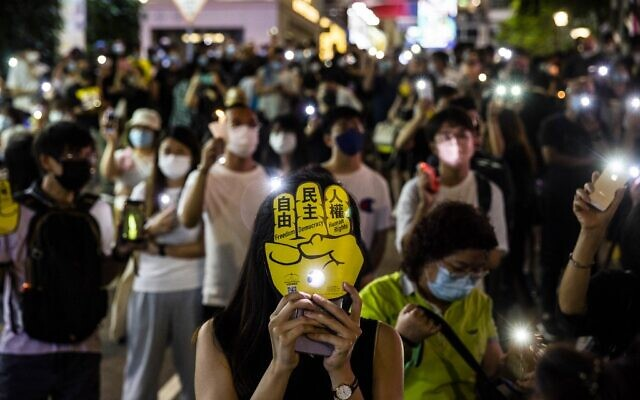 People hold up their phones with the light on in the Causeway Bay district of Hong Kong on June 4, 2021, after police closed the venue where Hong Kong people traditionally gather annually to mourn the victims of China's Tiananmen Square crackdown in 1989 which the authorities have banned citing the coronavirus pandemic and vowed to stamp out any protests on the anniversary. (ISAAC LAWRENCE / AFP)