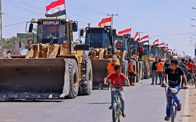 Palestinian boys cycle past a convoy of bulldozers provided by Egypt arriving at the Palestinian side of the Rafah border crossing between Egypt and the Palestinian Gaza Strip enclave on June 4, 2021 (SAID KHATIB / AFP)