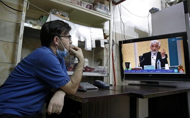 An Iranian vendor watches candidate Saeed Jalili speaking during the first televised debate between Iran presidential candidates, at a shop in Tehran on June 5, 2021. (AFP)