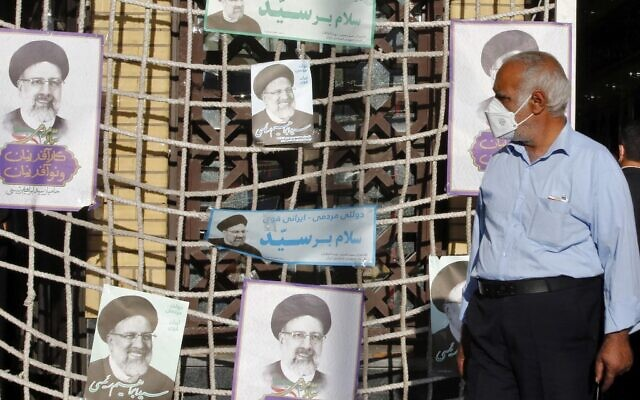 Illustrative: A supporter of Iranian presidential candidate Ebrahim Raisi walks next to his posters during an election campaign rally in the capital Tehran, on June 10, 2021. (STR / AFP)