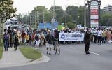 People march past the Cherryhill Village Mall parking lot where Nathaniel Veltman was arrested during the multi-faith march to end hatred, in London, Ontario, Canada, on June 11, 2021. (Nicole OSBORNE / AFP)