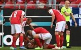 Denmark players help Denmark's midfielder Christian Eriksen after he collapsed before the medics arrive during the UEFA EURO 2020 Group B football match between Denmark and Finland at the Parken Stadium in Copenhagen on June 12, 2021. (Jonathan NACKSTRAND / various sources / AFP)
