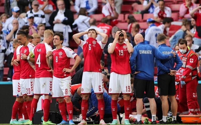 Denmark's players react and form a protective screen as paramedics attend to Denmark's midfielder Christian Eriksen after he collapsed on the pitch during the UEFA EURO 2020 Group B football match between Denmark and Finland at the Parken Stadium in Copenhagen on June 12, 2021. (Friedemann Vogel / POOL / AFP)