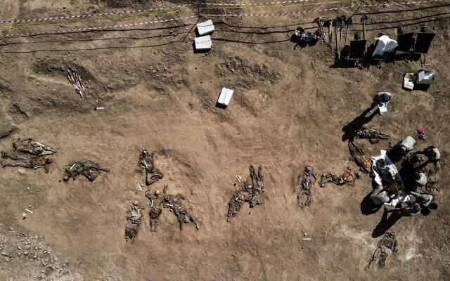 This aerial view taken on June 13, 2021, shows human remains, reportedly of victims of the 2014 Badush prison massacre committed by the Islamic State (IS) group, after being unearthed from a mass grave in the northern Iraqi village of Badush, northwest of the city of Mosul. (Zaid AL-OBEIDI/AFP)