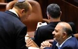 Israel's new Prime Minister Naftali Bennett (L) talks with Mansour Abbas, head of the Islamic Raam party during a special session to vote on the new government at the Knesset in Jerusalem, on June 13, 2021. (EMMANUEL DUNAND/AFP)