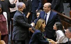 (L to R) Israel's outgoing prime minister Benjamin Netanyahu shakes hands with his successor, incoming Prime Minister Naftali Bennett, after a special session to vote on a new government at the Knesset in Jerusalem, on June 13, 2021. (EMMANUEL DUNAND / AFP)