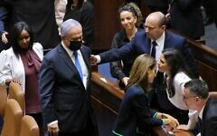 Defeated prime minister Benjamin Netanyahu walks away after briefly shaking hands with new Prime Minister Naftali Bennett, after the Knesset voted confidence in Bennett's coalition by 60-59 votes, June 13, 2021 (Emmanuel Dunand / AFP)