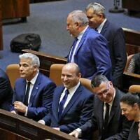 Sitting from left to right: Defense Minister Benny Gantz, Foreign Minister Yair Lapid, Prime Minister Naftali Bennett, Justice Minister Gideon Sa'ar, Transportation Minister Merav Michaeli and Health Minister Nitzan Horowitz, as Finance Minister Avigdor Lieberman and Housing Minister Ze'ev Elkin walk past after a special Knesset plenum session to approve the new government, June 13, 2021. (Emmanuel Dunand/AFP)