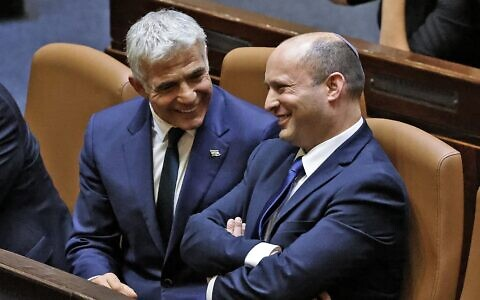 Prime Minister Naftali Bennett (right) and Foreign Minister Yair Lapid in the Knesset, on June 13, 2021. (Emmanuel Dunand/AFP)
