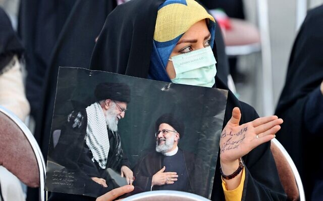 A supporter of Iranian presidential candidate Ebrahim Raisi holds a picture of him with Iran's Supreme Leader Ayatollah Ali Khamenei during an election campaign rally in the capital Tehran, on June 14, 2021. (Photo by ATTA KENARE / AFP)