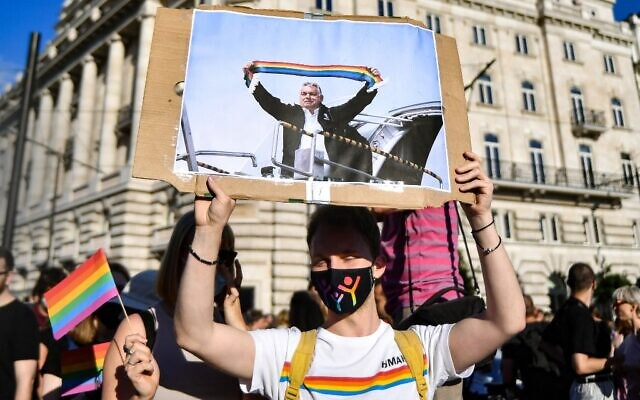 """A participant holds a placard showing Hungarian Prime Minister Viktor Orban holding a scarf in rainbow colors, in front of the parliament building in Budapest on June 14, 2021, during a demonstration against the Hungarian government's draft bill seeking to ban the """"promotion"""" of homosexuality and sex changes. (Photo by GERGELY BESENYEI / AFP)"""