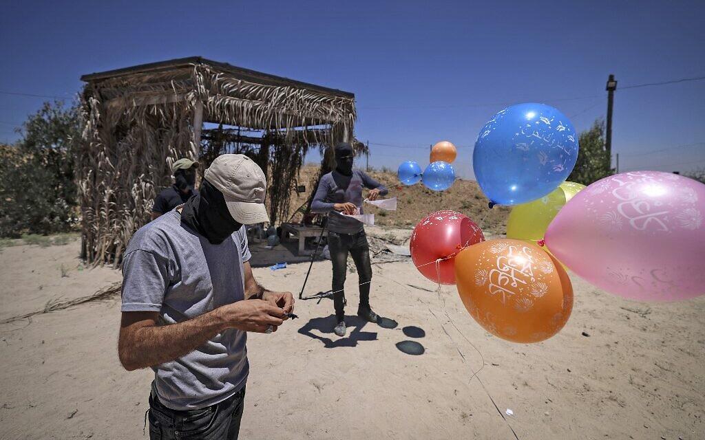 Masked Palestinian Islamic Jihad terrorists prepare incendiary balloons east of Gaza city, to launch across the border fence towards Israel on June 15, 2021. (MAHMUD HAMS / AFP)