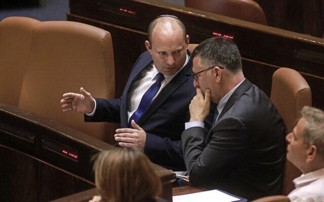 Prime Minister Naftali Bennett (left) speaks with Justice Minister Gideon Sa'ar in the Knesset on June 16, 2021. (Menahem Kahana / AFP)