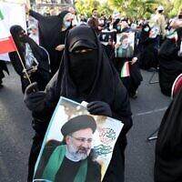 A supporter of Iranian ultraconservative presidential candidate Ebrahim Raisi carries a portrait and waves a national flag during a rally in the capital Tehran, on June 16, 2021, ahead of the June 18 presidential election (ATTA KENARE / AFP)