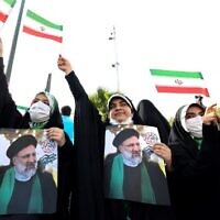 Supporters of Iranian ultraconservative presidential candidate Ebrahim Raisi carry posters bearing his portrait and wave national flags as they attend a rally in the capital Tehran, on June 16, 2021, ahead of the Islamic republic's June 18 presidential election.  (Photo by ATTA KENARE / AFP)