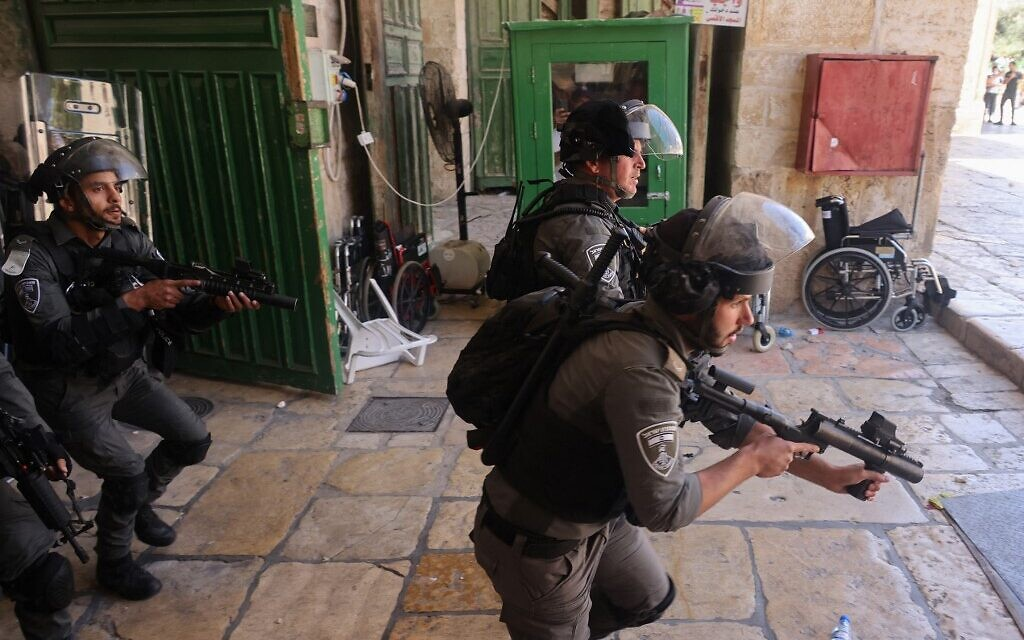 Members of the Israeli security forces take aim with tear gas launchers during a protest by Palestinians following Friday prayers at the Al-Aqsa mosque compound atop Temple Mount in Jerusalem, on June 18, 2021. (AHMAD GHARABLI / AFP)