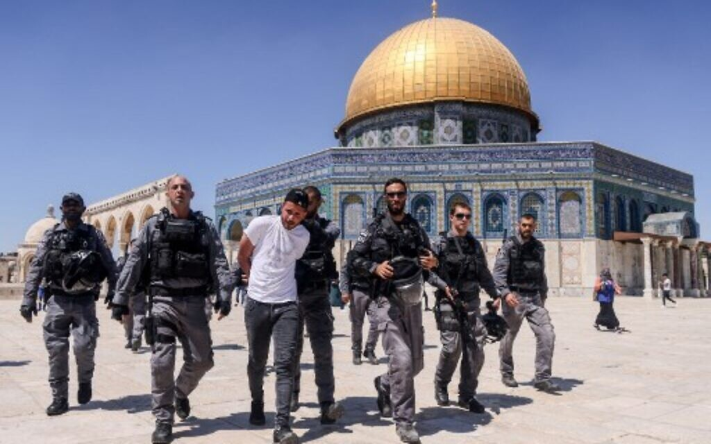 Israeli police arrest a Palestinian man in front of the Dome of the Rock shrine on the Temple Mount compound in Jerusalem on June 18, 2021. (Photo by AHMAD GHARABLI / AFP)