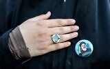 A woman holds her hand to her chest next to a pin bearing the image of Iran's newly-elected president Ebrahim Raisi during a rally celebrating his victory in Imam Hussein square in the capital Tehran on June 19, 2021. (ATTA KENARE / AFP)