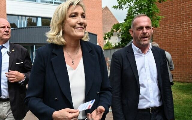 French far-right Rassemblement National (RN) Party leader and MP Marine Le Pen (L) and RN mayor of Henin-Beaumont Steeve Briois (R) leave a polling station in Henin-Beaumont, northern France, for the first round of the French regional elections on June 20, 2021. (DENIS CHARLET/AFP)