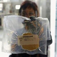 A technician displays lab-grown chicken meat in a sealed bag at the food-tech startup SuperMeat in the central town of Ness Ziona on June 18, 2021 (JACK GUEZ / AFP)